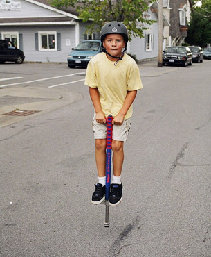 a boy jumping on a pogo stick on the street